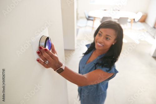 Canvas Print Woman Adjusting Digital Central Heating Thermostat At Home