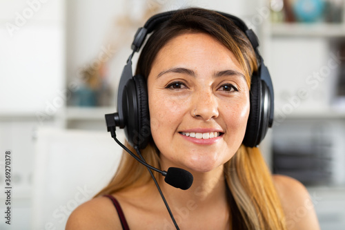 Fotografija Portrait of young smiling latina woman with headset at call center office