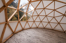 Interior Of Large Geodesic Wooden Dome Tent With Window And View To Forest. Empty Interior Glamping Tent.