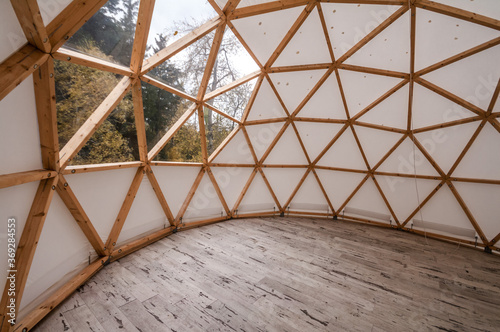 Valokuvatapetti Interior of large geodesic wooden dome tent with window and view to forest