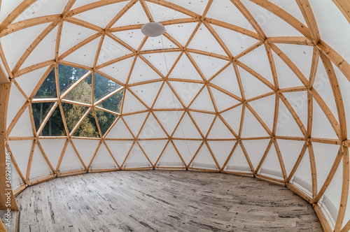 Interior of large geodesic wooden dome tent with window and view to forest Fototapet
