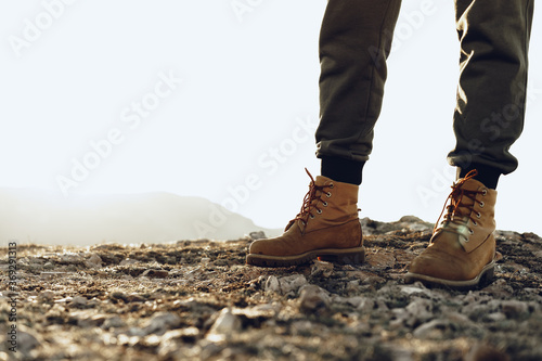 Fotografiet Legs of a backpacker in hiking boots standing on the top of the mountain