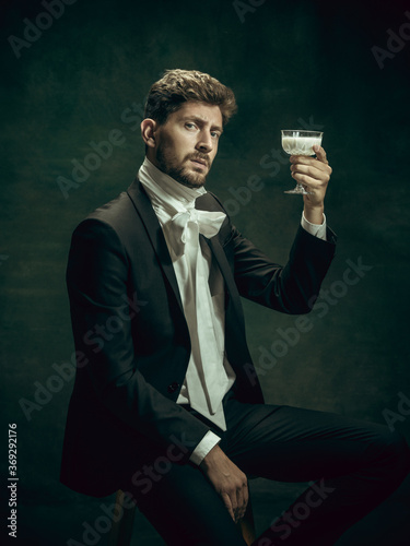 Obraz Drinking liquor. Young man in suit as Dorian Gray isolated on dark green background. Retro style, comparison of eras concept. Beautiful male model like classic literature character, old-fashioned. - fototapety do salonu