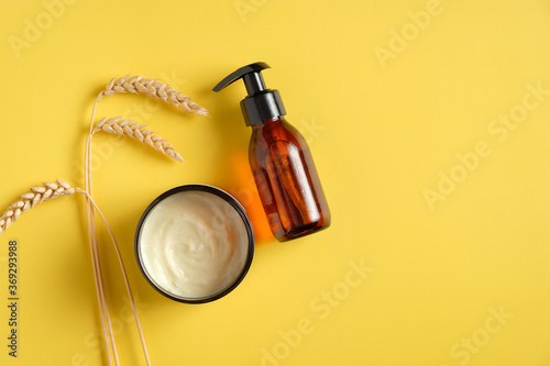 Dark amber glass pump cosmetic bottle, moisturizer cream in jar, wheat on yellow background Fototapeta