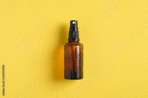 Canvas Print Wet amber glass spray bottle mockup with water drops on yellow background, view from above