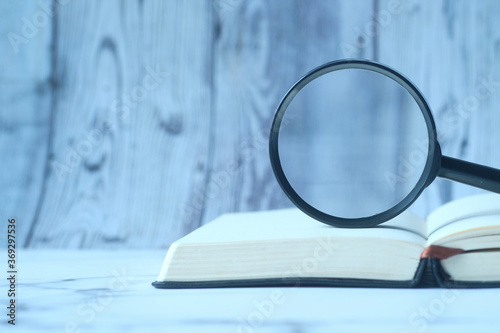 Tableau sur Toile open book and magnifying glass on table.