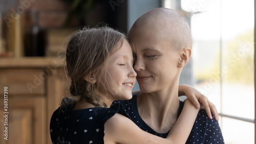 Fotografía Happy young Caucasian cancer patient sick mother and little daughter hug show lo