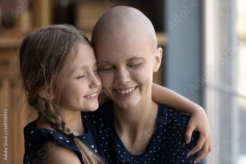 Fotografia Close up of loving little Caucasian daughter hug sick cancer patient hairless ba