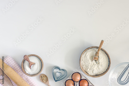 Slika na platnu Ingredients for home baking cookies butter, sugar, eggs, flour, cookie cutters, rolling pin on a light background, top view