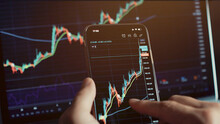 Investment Stockbroker Stock Market Analysis Data Graph With Price Rates. Stock Market Trader Analyzing Bitcoin Price Trend. Investment Broker Trading Bitcoin Crypto Currency Using Phone And Laptop