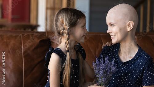 Fotografia Loving little Caucasian daughter congratulate sick cancer patient bald hairless