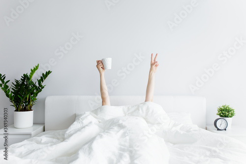 good morning concept - female hands with coffee cup and victory sign sticking ou Fototapeta