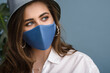 Woman wearing stylish protective blue face mask, trendy bucket hat, pearl earrings. Fashion accessory during quarantine of coronavirus pandemic. Close up studio portrait. Copy, empty space for text
