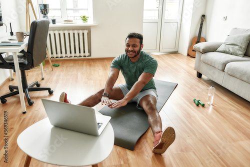 Fototapeta Cheerful stretching. Male fitness instructor showing exercises while streaming, broadcasting video lesson on training at home using laptop. Sport, online gym concept obraz