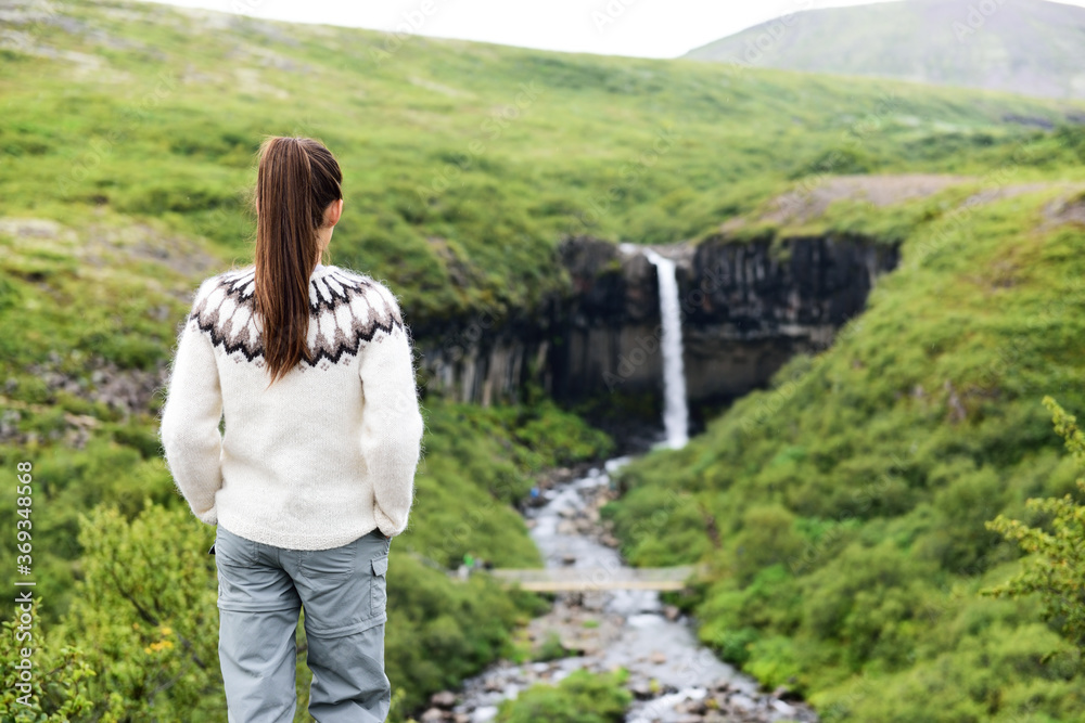 Fototapeta Iceland. Woman hiking looking at Svartifoss waterfall. Female is visiting famous tourist attraction of Iceland. Spectacular natural landmark on vacation in Skaftafell. Icelandic nature landscape.