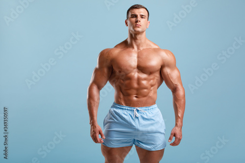 Foto Handsome muscular man naked torso abs, isolated on blue background