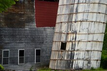 Leaning Silo With Old Barn Background