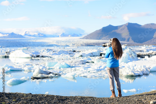 Fototapeta Photographer tourist woman taking photos with DSLR camera on travel on Iceland by Jokulsarlon glacial lagoon / glacier lake on Iceland. Happy tourist girl on travel in beautiful nature landscape. obraz
