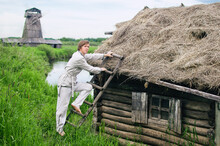 Village Young Man In White Linen Clothes Climbs Up A Ladder To The Thatched Roof Of A Small Hut