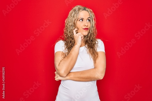 Fényképezés Young beautiful blonde woman wearing casual t-shirt standing over isolated red background with hand on chin thinking about question, pensive expression