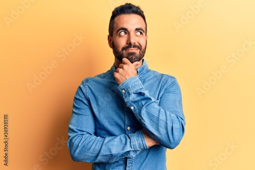 Young hispanic man wearing casual clothes with hand on chin thinking about question, pensive expression Tapéta, Fotótapéta