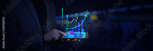 Slika na platnu business man tablet on hand candle stick graph chart.