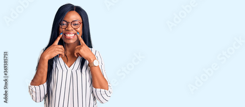 Young african american woman wearing casual clothes and glasses smiling with ope Canvas Print