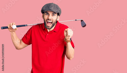 Fotografie, Obraz Young handsome man with beard playing golf holding club and ball screaming proud