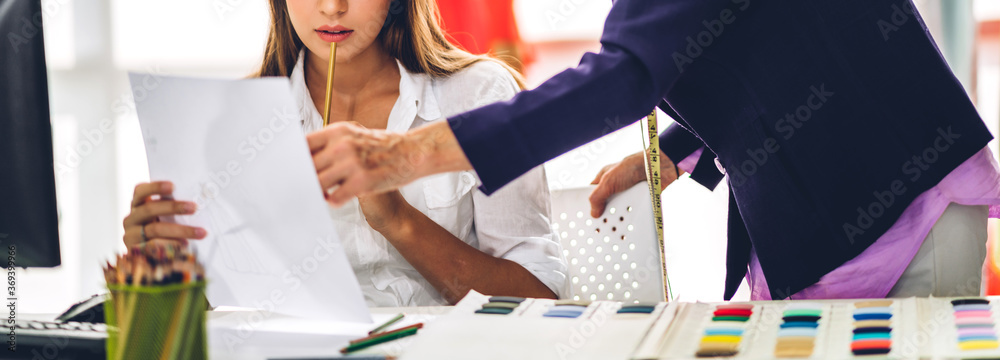 Fototapeta Portrait of woman fashion designer stylish sitting and working with color samples.Attractive woman working with mannequins standing and colorful fabrics at fashion studio
