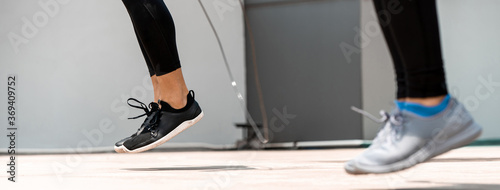 Vászonkép Legs of sports men doing jumping rope exercise outdoors on the floor, banner siz