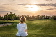 A Lonely Girl In A White Dress Sitting On Golf Course Looking At Sunset Sunrise Sun. Relaxing And Thinking About The Meaning Of Life