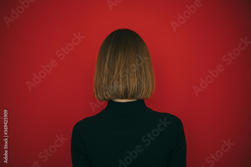 Woman in black sweater and with hairstyle bob isolated on red background, standing with her back to the camera Fotobehang