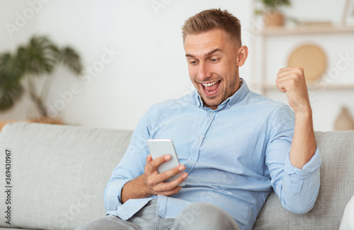 Obraz Excited male employee feeling ecstatic holding phone - fototapety do salonu