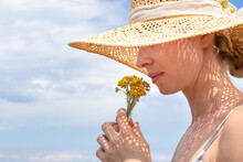 Portrait Of Young Beautiful Cheerful Woman Wearing Straw Sun Hat, Smelling Small Bouquet Of Yellow Wild Florets, Against Blue Summer Sky.