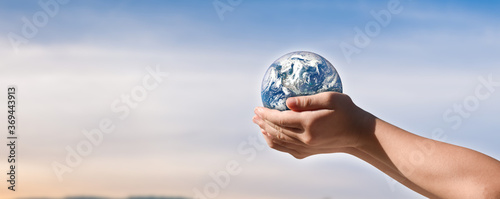 Fotografering environment day concept, Globe in child hands over blue sky background