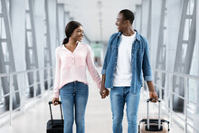 Just Married Black Couple Walking With Suitcases In Airport, Going To Honeymoon