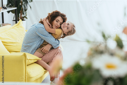 Foto selective focus of happy babysitter and child embracing while sitting on sofa