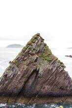 Beautiful Single Rock Formation On The Seashore, Triangle Shape, Dramatic Details, Sharp Edges With Misty Foggy Background, Sculpture By Ocean Waves