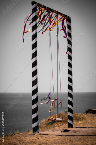 фотография large swing with colored ribbons on the cliff