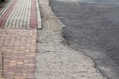 Fototapeta Chodnik z betonowych kolorowych kostek wraz z fragmentem asfaltowej drogi. obraz