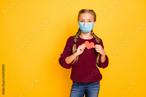Portrait of her she nice attractive pre-teen girl wearing safety gauze mask mers cov disease prevention holding in hand heart shape card isolated bright vivid shine vibrant yellow color background
