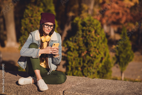 Portrait of her she nice attractive pretty focused cheery girl blogger using 5g app device browsing post share social network blogging spending sunny day October outdoor outside fresh air