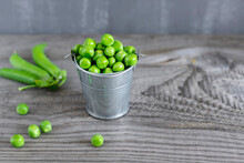 Close-up View Of Fresh Green Peas In A Small Metal Bucket On Dark Wooden Table.