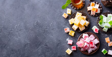 Assortment Of Turkish Delights With Glass Of Tea. Grey Background. Copy Space. Top View.