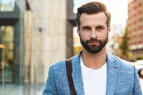 Foto Attractive young bearded man walking outdoors