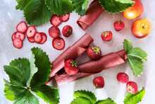 Natural Strawberry Pastille Is Rolled Into A Cone And Into Tubes. Dainty And Berries On A Light Background With Strawberry Leaves. Copy Of The Space. Flat Layout.