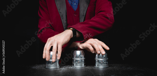 Canvas Print Magician shows shell game of thimbles with circles and ball, black background