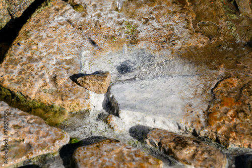 Photo Mineral deposition on stones by dripping water from a healing spring