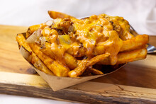 A View Of A Basket Of Loaded Fries, On A Wooden Cutting Board, In A Restaurant Or Kitchen Setting.