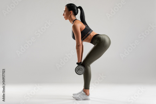 Fototapeta Fitness woman doing exercise for glutes on gray background